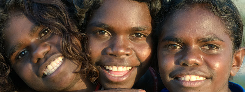 Three young Aboriginal children smiling at camera