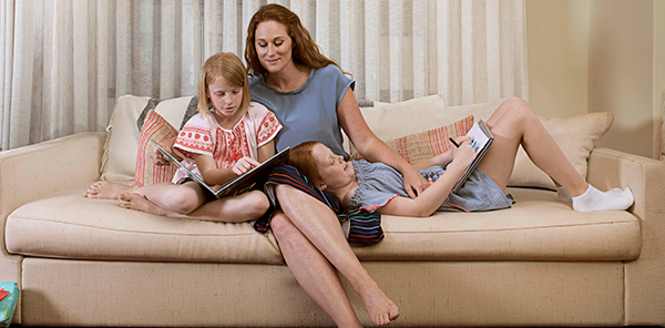 Mother and two daughters sitting on a couch reading