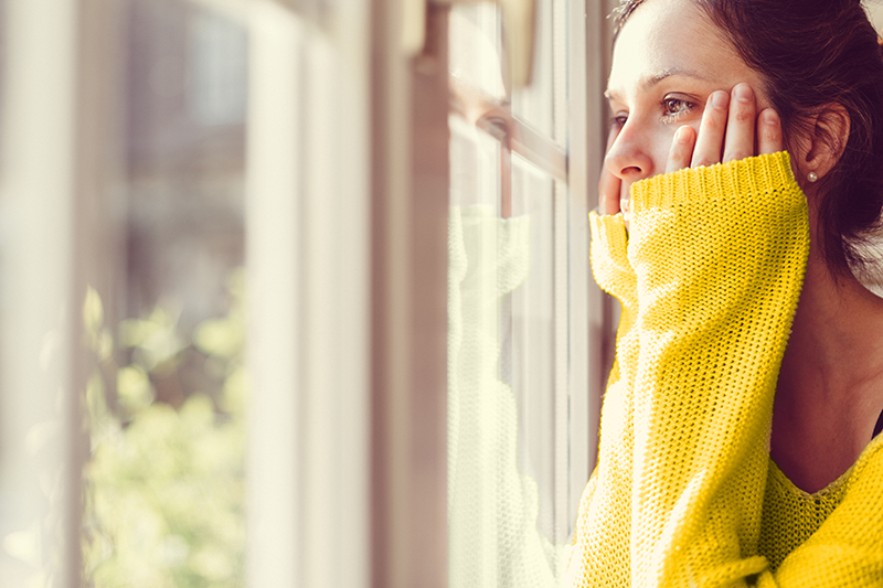 woman in yellow jumper looking out of window