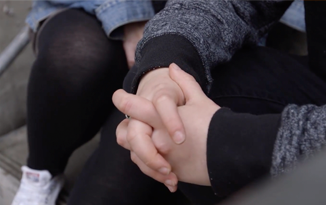 Young person holding hands
