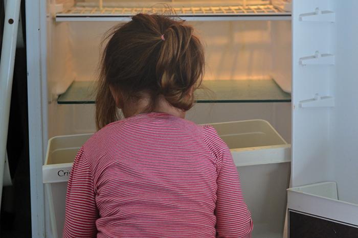 Young girl looking into empty fridge