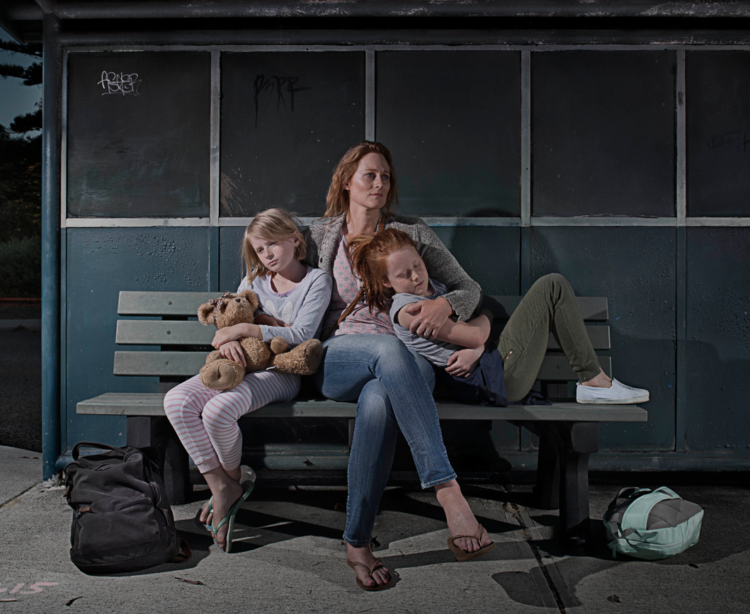 Mother and young daughters looking sad at bus stop