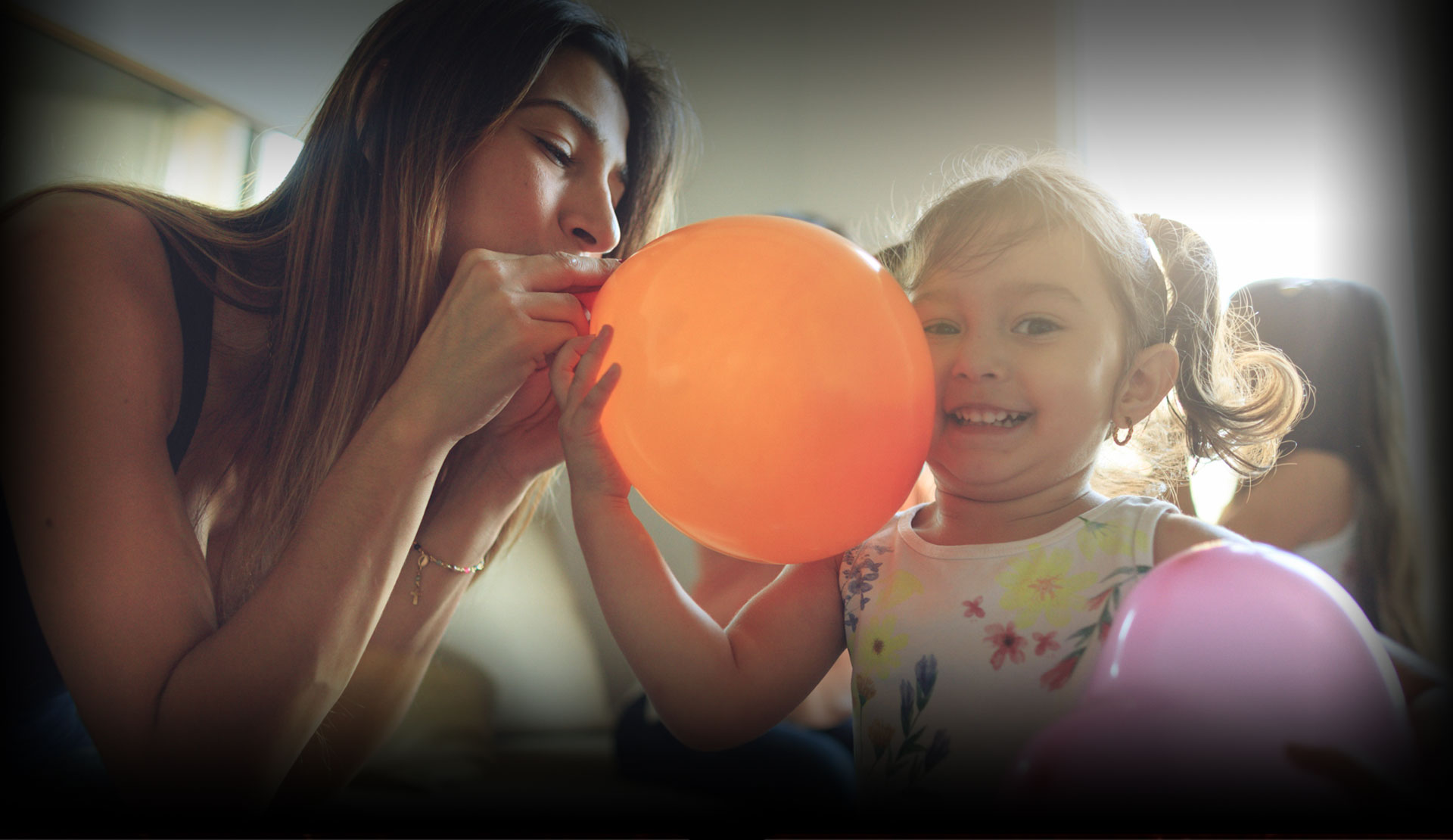 Young mother and daughter playing with balloon