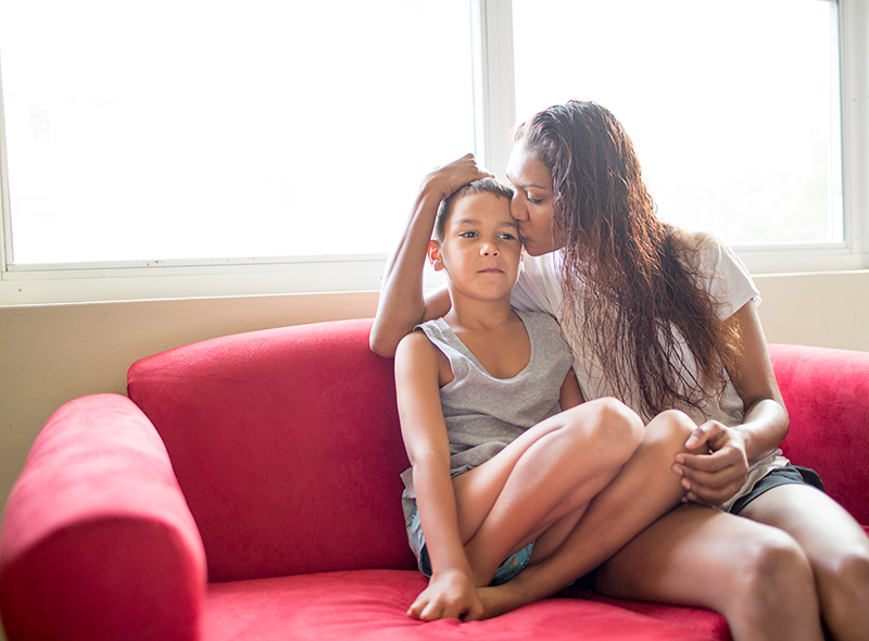 Aboriginal mother and son sitting on couch